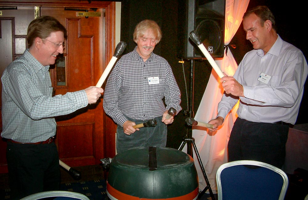 Delegates playing barrel drums - team building drum energisers in Europe