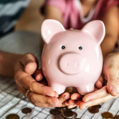 stock photo of woman holding piggy bank
