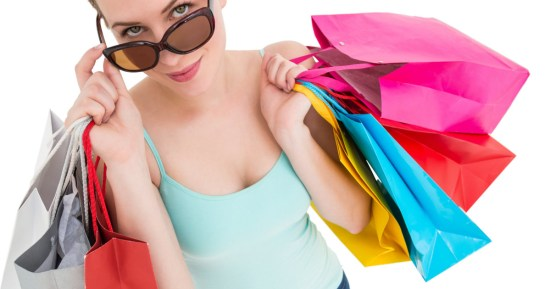 stock photo of a white woman holding 7 colorful shopping bags and sunglasses
