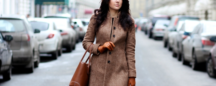 professional young woman walking down a street wearing a stylish interview coat