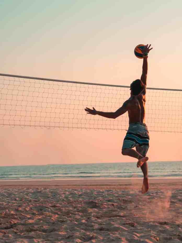 Homme jouant au volley sur la plage
