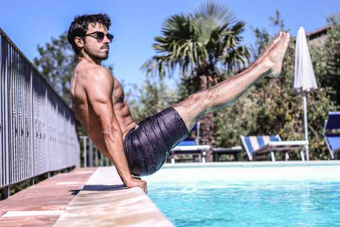 Homme faisant un gainage au bord d'une piscine