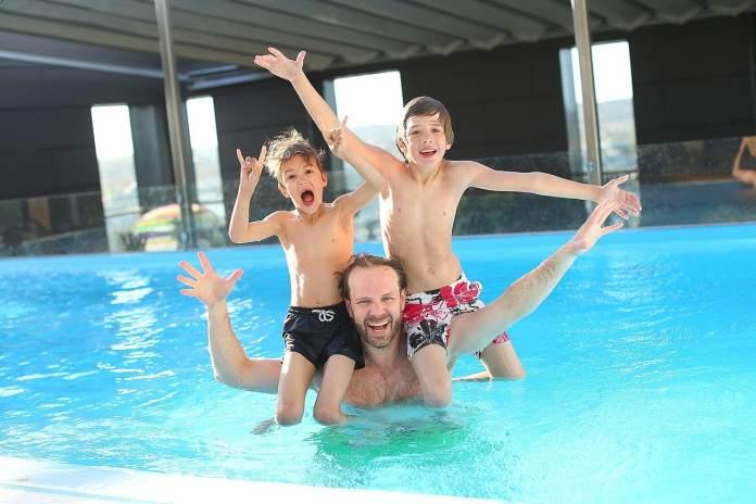 Un père et ses fils à la piscine