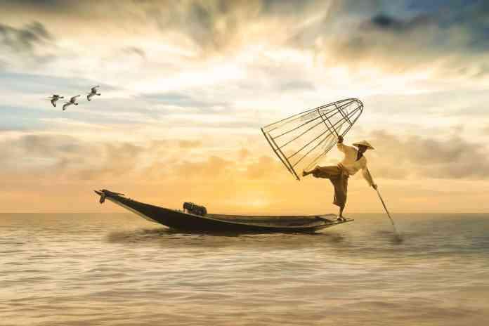 Pécheur sur barque sur une jambe