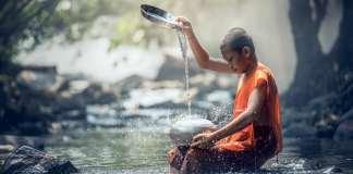 Moine jouant du bol chantant dans la rivière