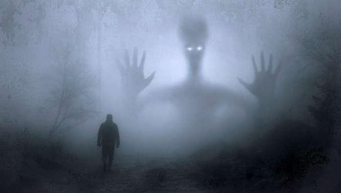 Homme marchant dans le brouillard avec une ombre de immense devant lui