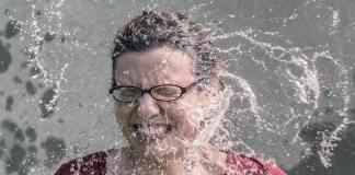 Femme recevant de l'eau sur le visage