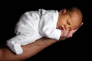 Bébé qui dort sur le bras de son père