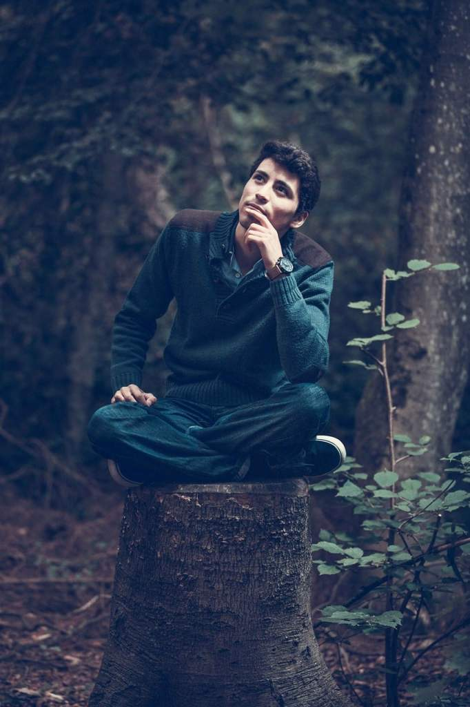 Homme qui pense sur un tronc d'arbre
