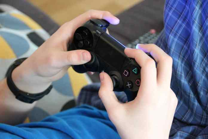 Mains sur une manette de PS4
