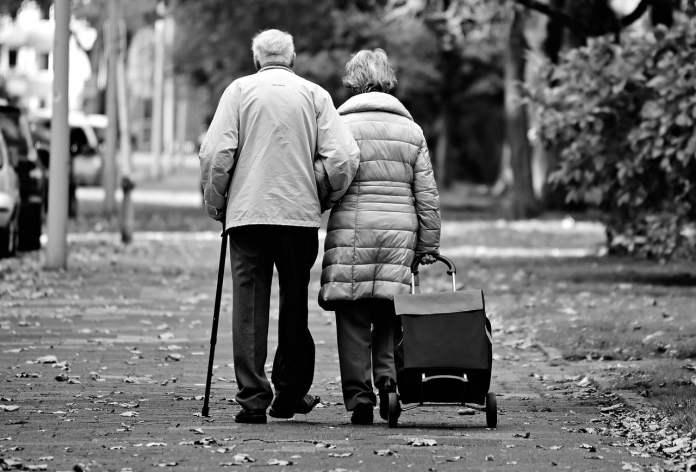 Couple de personnes âgées marchant de dos