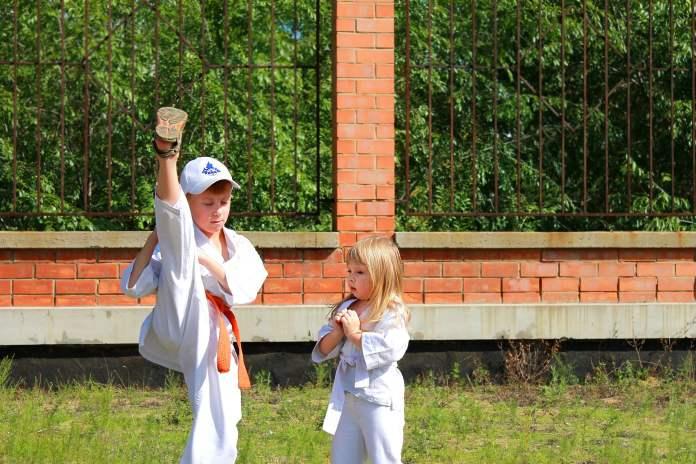 Enfant qui montre a un autre comment faire un mouvement