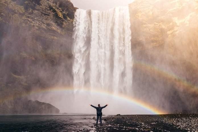Homme devant une cascade avec un arc-en-ciel