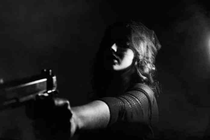 Femme qui tend un pistolet