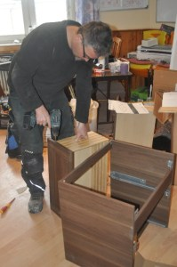 Chris assembling cabinets with instructions in German