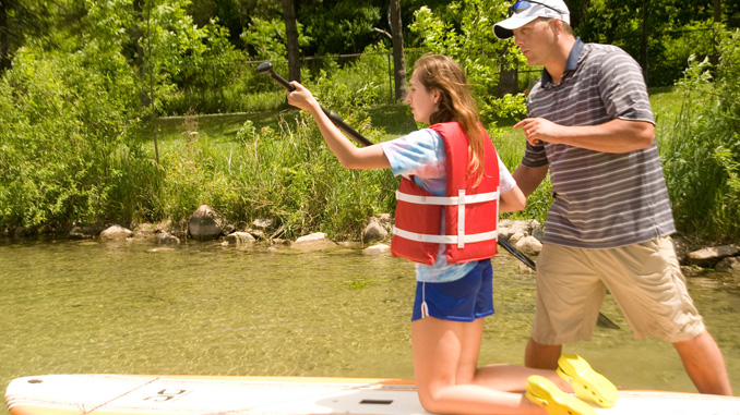 Homer High School teacher Geoff Sorenson helps junior Lindsey Sovocool use a paddle board Monday at Durkee Park in Homer as part of an outdoor-oriented gym glass. The outdoor gym class, an elective for juniors and seniors, provides opportunities to learn proper boating techniques, what to do in an emergency, how to fish and general safety tips.