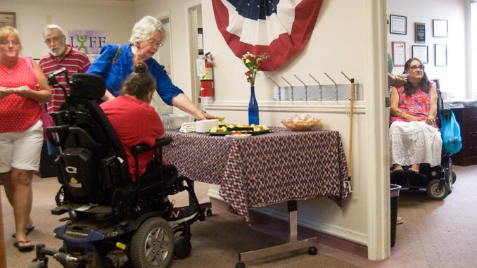 Fran Pizzola, community education coordinator at Access to Independence, right, chats in her office as others help themselves to snacks Tuesday during the center's celebration of the 26th anniversary of the Americans with Disabilities Act.