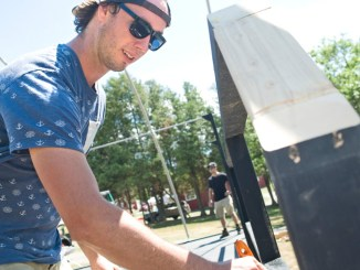 Tyler Coakley, Seedstock music festival organizer, puts the finishing touches on the main stage Saturday on Route 215 in Cortlandville. Seedstock, set for this weekend, is expanding to three days, will have almost double the bands and is offering camping.
