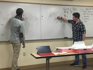 Two members of the Biochemisty Club play Pictionary during a game night.
