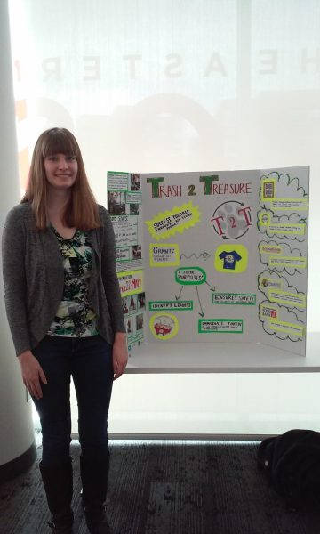 Sarah Braun stands in front of a poster for Trash to Treasure