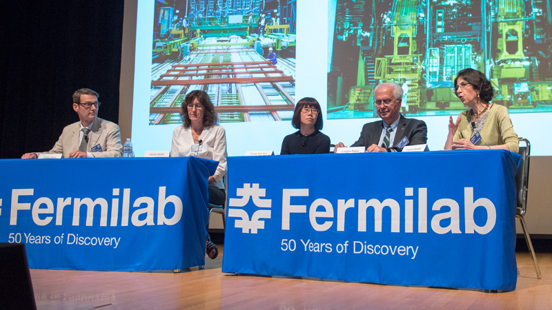 Four people sitting on a panel on a stage with a Fermilab tablecloth draped over the table.