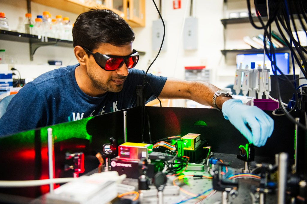 A student works on a piece of machinery in the nanoscale biophysics lab.