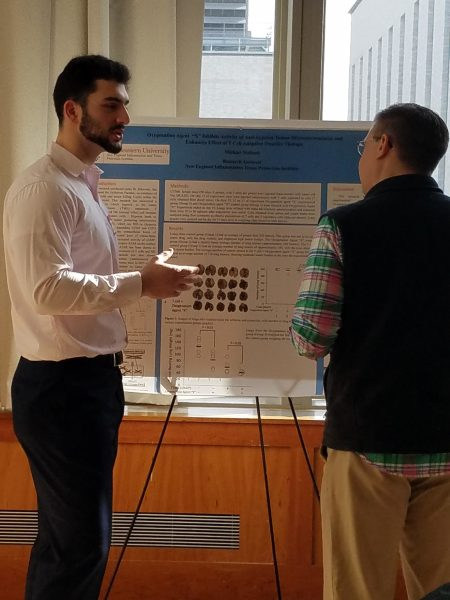 Michael Mallouh talks with another person while standing in front of a scientific poster.