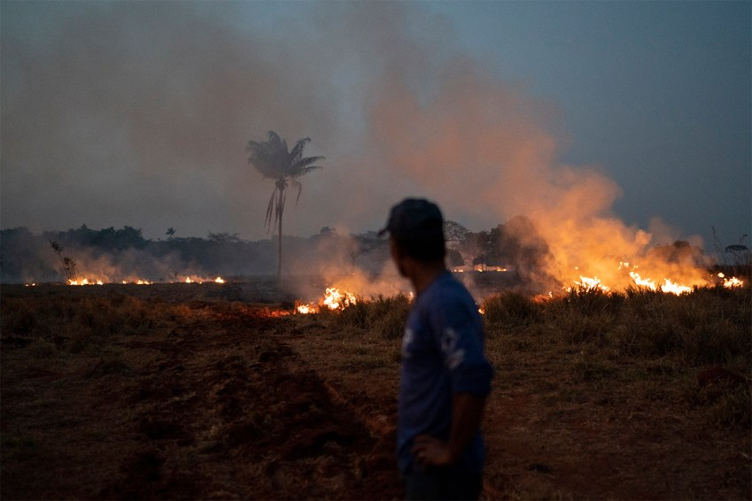 Neri dos Santos Silva watches an encroaching fire threat after digging trenches to keep the flames from spreading to the farm he works on, in the Nova Santa Helena municipality, in the state of Mato Grosso, Brazil, Friday, Aug. 23, 2019. Under increasing international pressure to contain fires sweeping parts of the Amazon, Brazilian President Jair Bolsonaro on Friday authorized use of the military to battle the massive blazes. (AP Photo/Leo Correa)