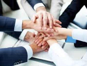 Image of multiple hands placed one on top of the other as a group handshake