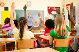 children raising hands in class setting