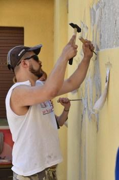 Andrea Mastrovito scalpella il muro del Cappello d'oro