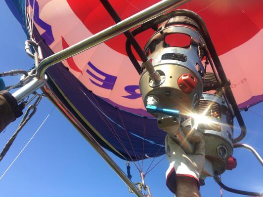 La mano del pilota che aziona il bruciatore della mongolfiera