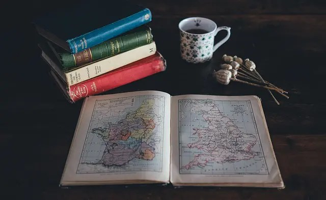 An open atlas with other books and a cup of tea. Expats and immigrants.
