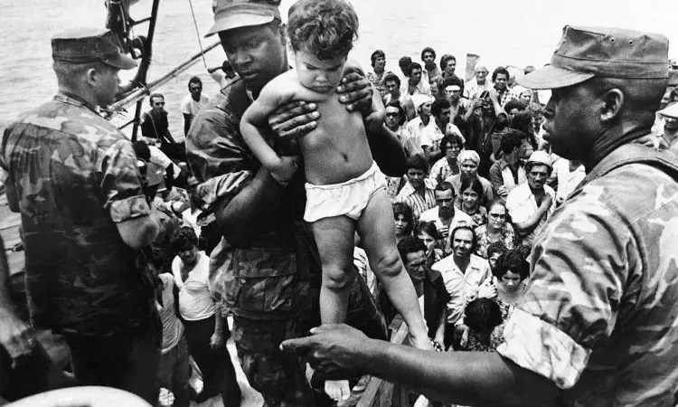 A U.S. Marine helps a child off one of the refugee boats during the Mariel Boatlift in 1980.