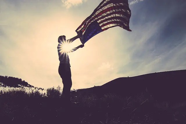 Man waving an American flag in a field at sunset. American individualism and Australian mateship.