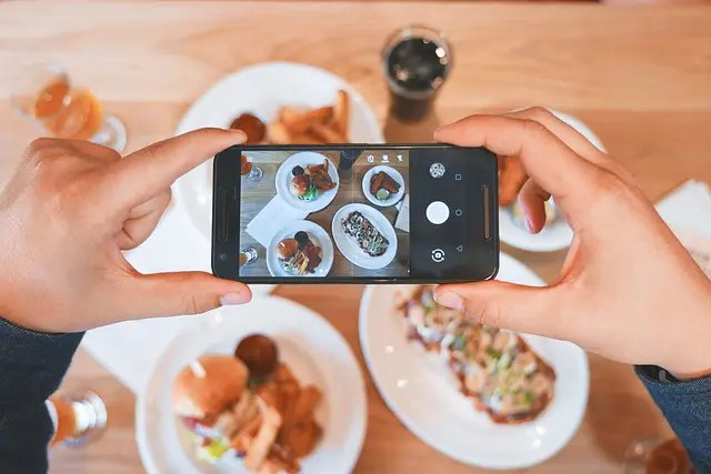 Two hands holding a smartphone photographing their food.