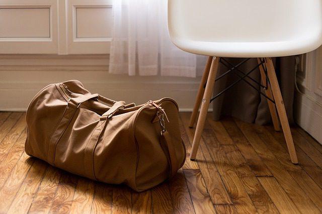 Between cultures. Suitcase on the floor.