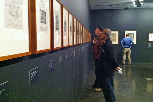 Visitors looking at William Blake's Illustrations of the Book of Job.