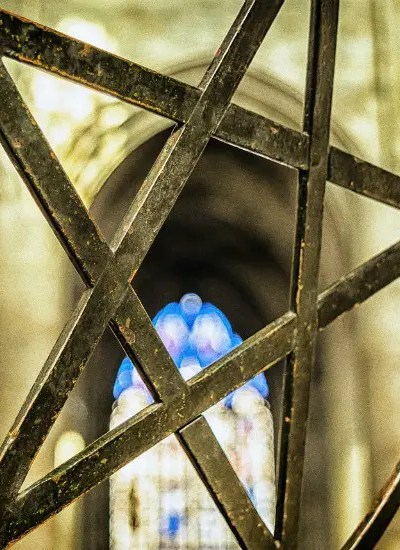 A pentacle against glass stained windows of a church.