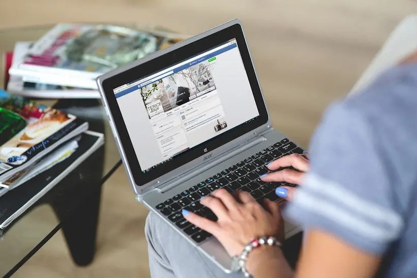 A woman's hands using a laptop, on Facebook.