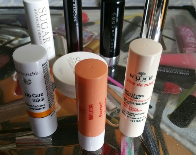 Left to right: Weleda Everon Lip Balm, Dr. Hauschka Lip Care Stick, and Nuxe Reve de Miel Lip Moisturizing Stick; Back and middle: Balms reviewed in Parts 1 and 2