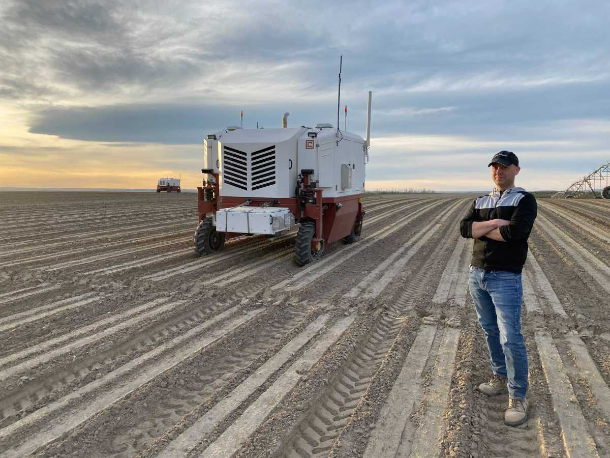 Carbon Robotics CEO Paul Mikesell and robot in farm field