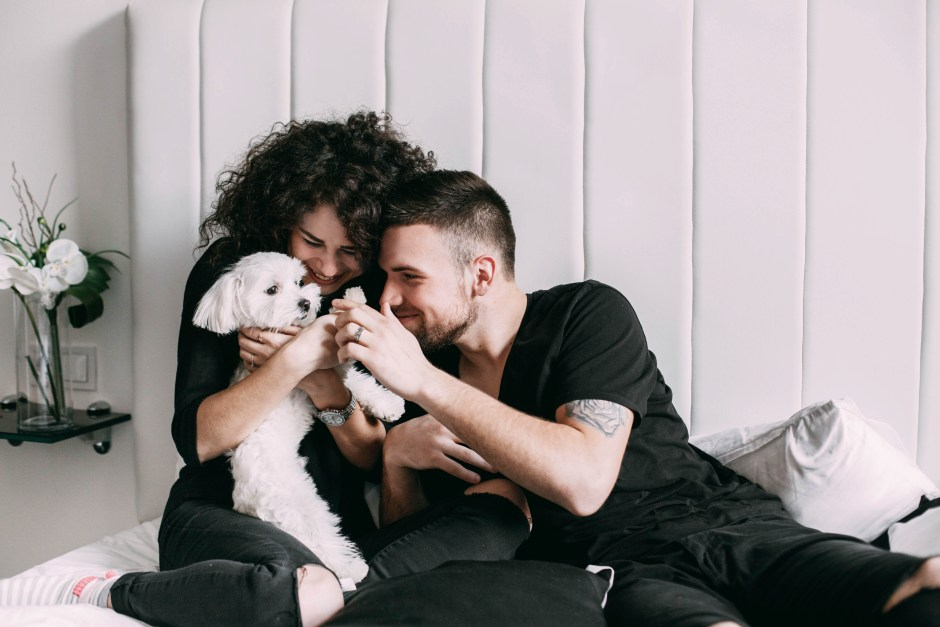 Man and woman in black play with little Maltese white dog on bed