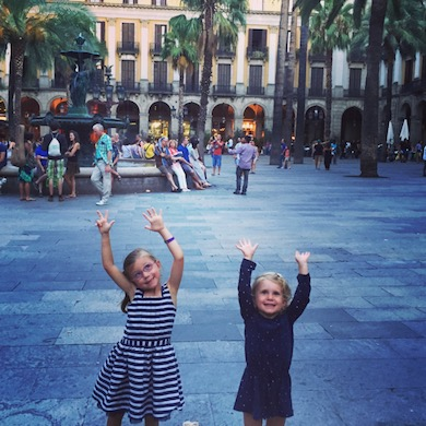Family travel - travel with kids for an added dimension - happy kids in Barcelona - hands up on Plaça Reial