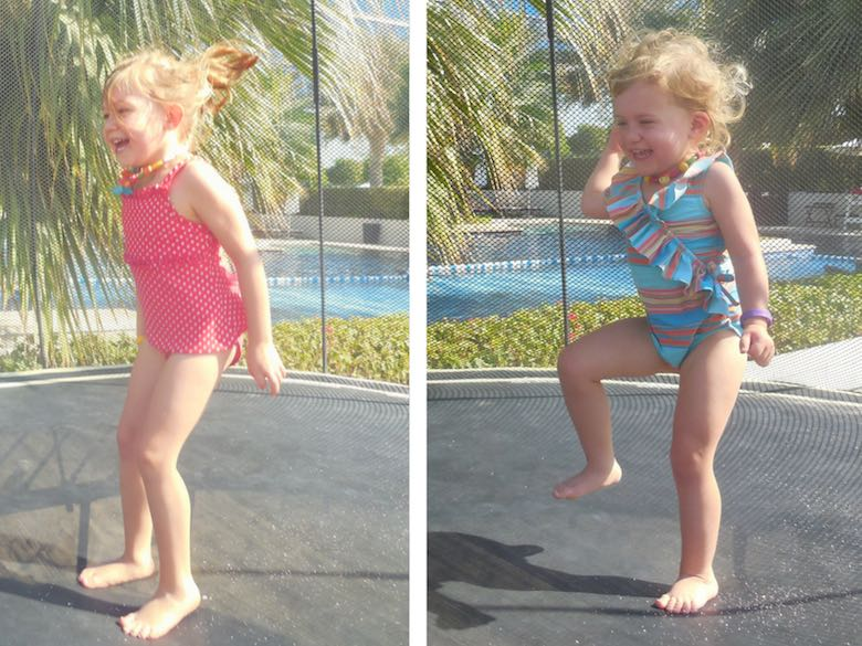 Two CosmopoliClan girls having fun while jumping on the trampoline against the backdrop of the pool of the Fairmont Bab Al Bahr hotel in Abu Dhabi
