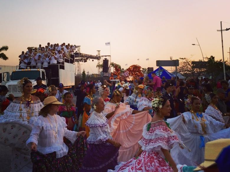 Local ladies dancing in their colorful traditional pollera dress during the carnival parade in Panama by sunset