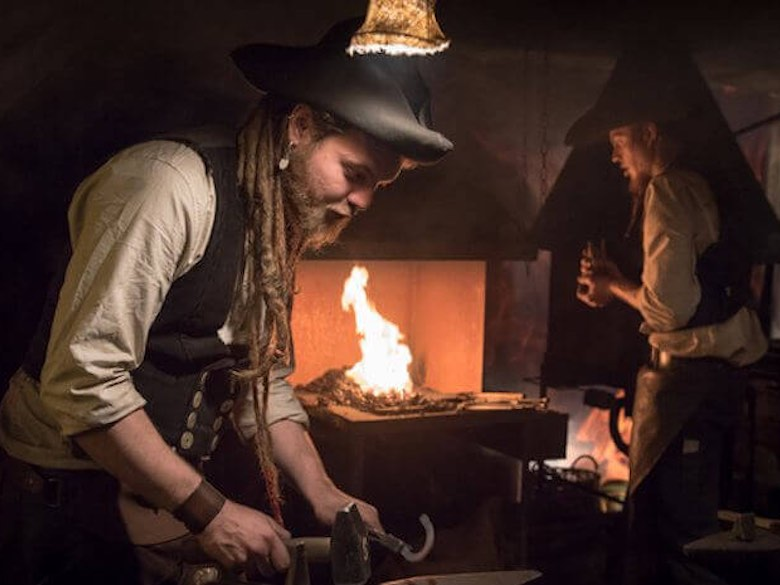 Two blacksmiths working by the flame at the Christmas market of Altstadt Cologne in Germany