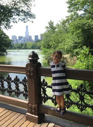 Little girl standing on a bridge in Central Park overlooking the lake and the Manhattan skyline