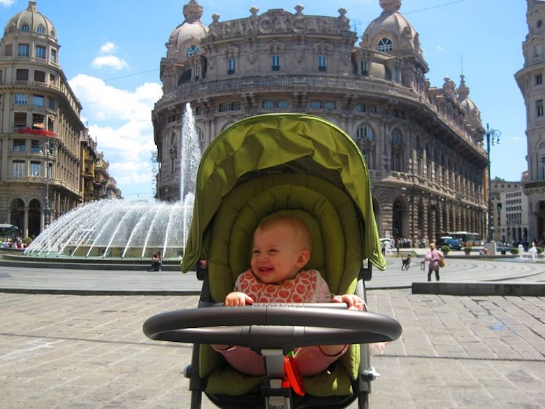Baby girl in a stroller having fun by the fountain on the Piazza De Ferrari in Genoa showing how fun it is to visit Italy with kids