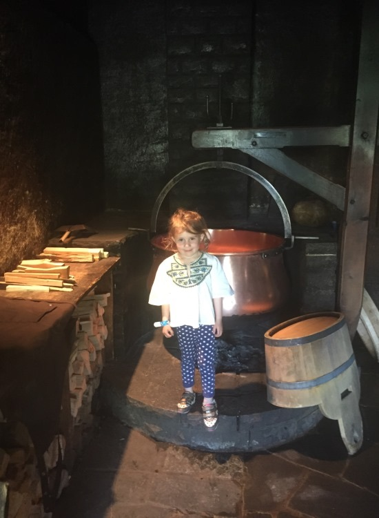 Little girl posing with big traditional cheese-making attributes in the Emmentaler Schaukäserei or Cheese Showdairy in Affoltern, Switzerland